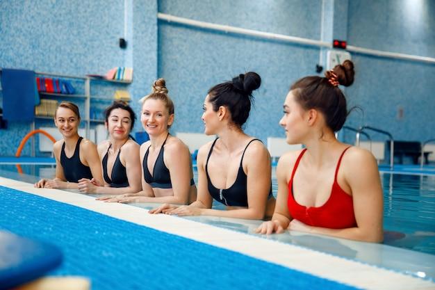 Vrouwelijke zwemmers groep poseert bij het zwembad