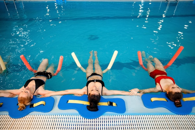 Vrouwelijke zwemmersgroep, aqua-aerobicstraining bij het zwembad