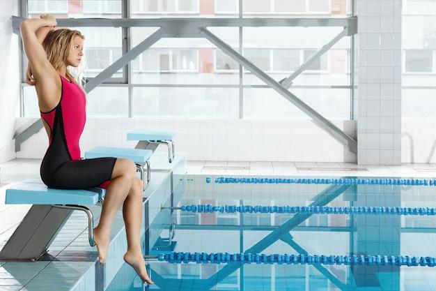 Vrouwelijke zwemmerszitting naast een pool