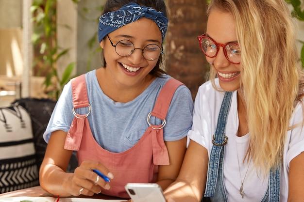 Vrouwelijkheid, technologieconcept. positieve interraciale lachende vrouwen werken samen om een vreemde taal te leren