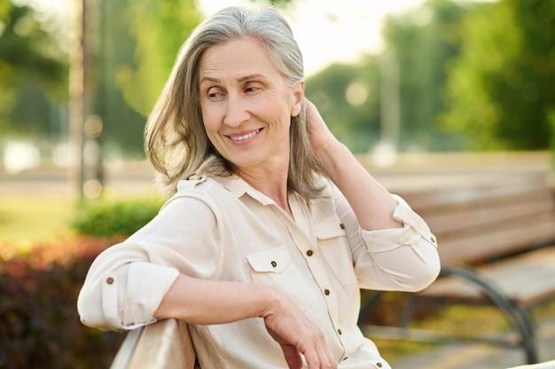 Vrouwelijkheid. vrolijke schattige volwassen blonde vrouw terugkijkend zittend op een bankje op zomerdag