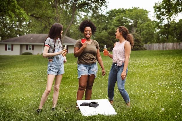 Vrouwen aan het kletsen tijdens een cornhole-spel in het park