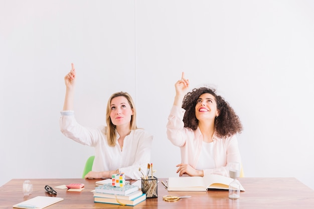 Vrouwen aan tafel wijzen omhoog
