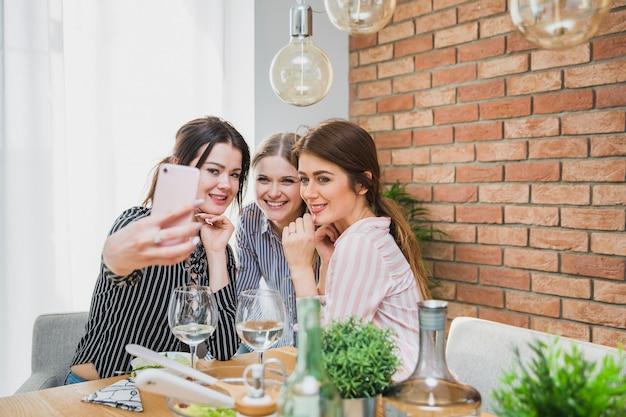 Vrouwen aan tafel zitten en nemen selfie
