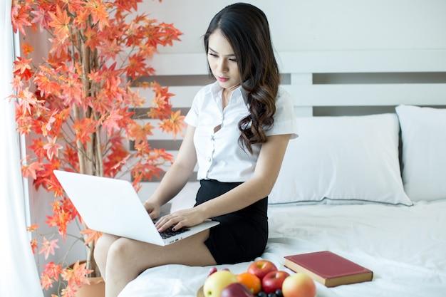 Vrouwen aankleden studentuniformen bekijkt een film vanaf een laptop