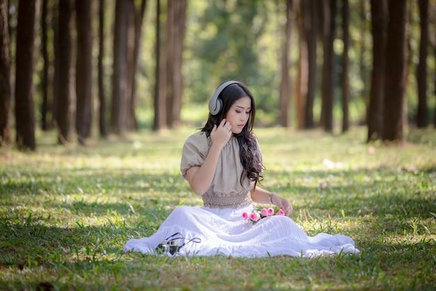 Vrouwen aziatisch meisje die met hoofdtelefoons de digitale muziek van bluetooth in het park luisteren