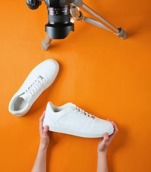 Vrouwen beoordelen nieuwe witte sneakers met camera op statief op oranje achtergrond. bovenaanzicht. minimalisme Premium Foto