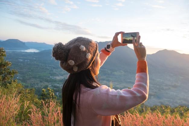 Vrouwen bergzicht en maak een foto met een smartphone