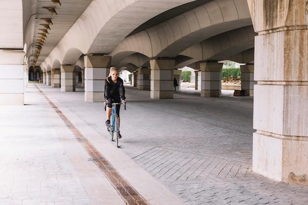 Vrouwen berijdende fiets onder brug