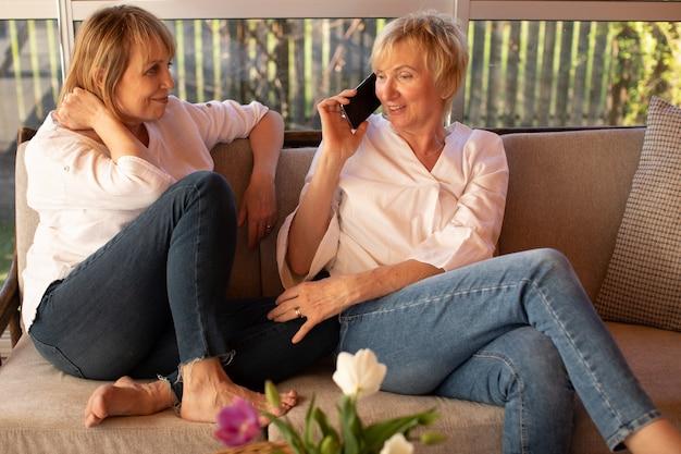 Vrouwen bestellen online eten terwijl ze op de veranda van een houten huis zitten met behulp van een smartphone