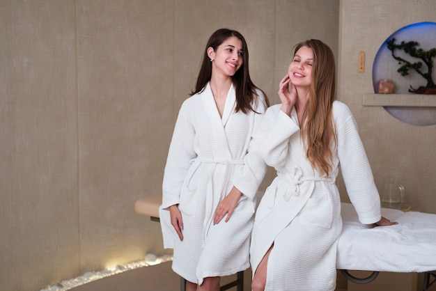 Vrouwen bij kuuroord het stellen in badjassen