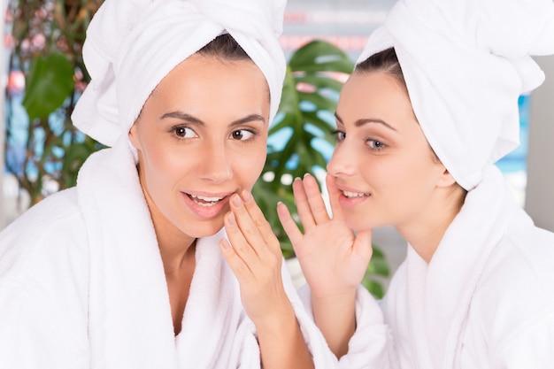 Vrouwen bij kuuroord. twee mooie jonge vrouwen in badjassen roddelen