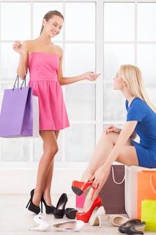 Vrouwen bij schoenenwinkel. twee mooie jonge vrouwen passen schoenen in een schoenenwinkel