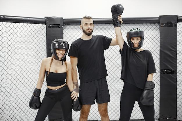 Vrouwen boksen. rechter maakt de winnaar bekend. dame in zwarte sportkleding. vrouwen met coach.