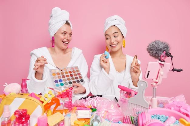 Vrouwen brengen make-up aan gebruik cosmetisch penseel en spons houden oogschaduwpalet zeer tevreden voelen geven tips over er mooi uitzien uitzending online streaming video voor blogvolgers