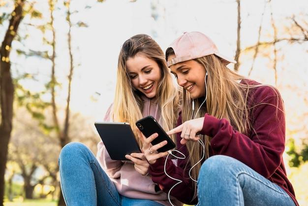 Vrouwen buiten in park met behulp van mobiele telefoons