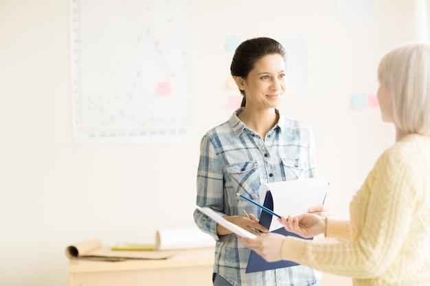 Vrouwen chatten op kantoor en glimlachen