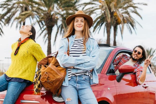 Vrouwen dichtbij mens die uit auto leunen en vredesgebaar tonen