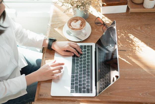 Vrouwen die aan de tafel werken met behulp van laptop krijgen een aantal ideeën in het café