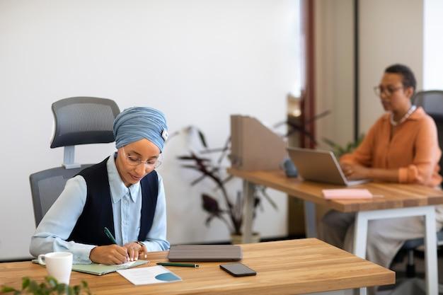 Vrouwen die aan het bureau werken voor een kantoorbaan
