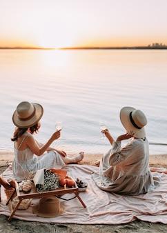 Vrouwen die aan zee ontspannen en wijn drinken bij zonsondergang