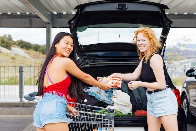 Vrouwen die aankopen in boomstam van auto in parkeerterrein zetten en camera bekijken