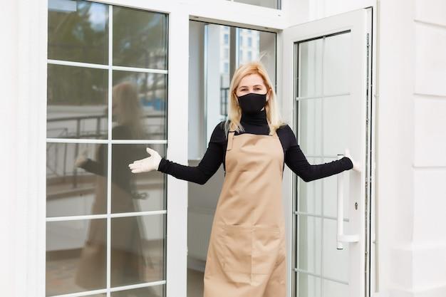 Vrouwen die beschermend masker dragen die zich in koffie bevinden tijdens covid-19 het voorkomen.