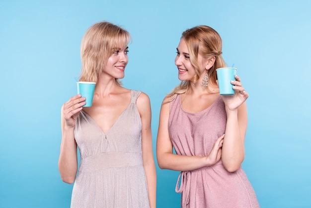 Vrouwen die bij elkaar studioschot glimlachen