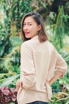Vrouwen die bruine overhemden dragen die in de tuin stellen