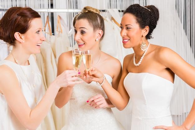 Vrouwen die champagne drinken terwijl bruidsjurk in de winkel van de huwelijksmode passen