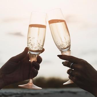 Vrouwen die champagneglazen op de achtergrond van zonsondergang houden