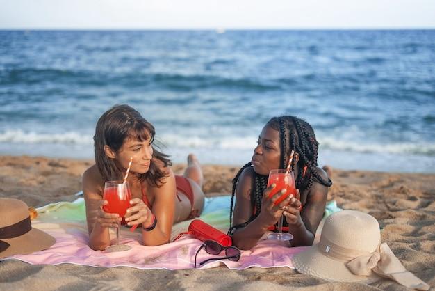 Vrouwen die cocktails drinken op het strand