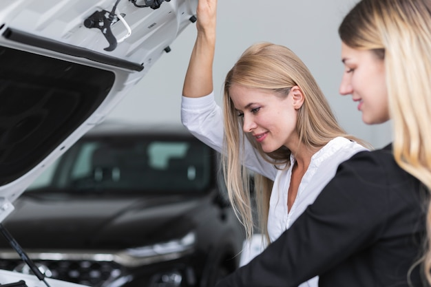 Vrouwen die de auto in de showroom controleren