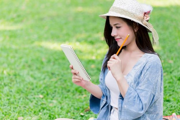 Vrouwen die de brief van het notascript in het document bij de tuin denken te schrijven