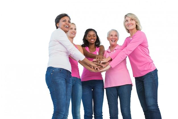 Vrouwen die de linten van borstkanker met handen dragen samen en glimlachend