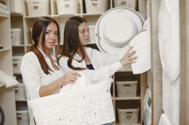 Vrouwen die de wasmachine gebruiken om de was te doen. jonge meisjes klaar om kleren te wassen. interieur, wasproces concept