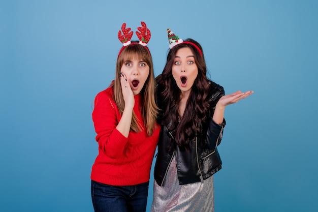 Vrouwen die de winterkleren en grappige die kerstmishoepels dragen over blauw worden geïsoleerd