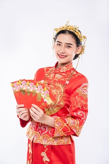 Vrouwen die een cheongsam-pak dragen, hebben veel geluk om op de traditionele dag cadeaugeld van ouders te krijgen