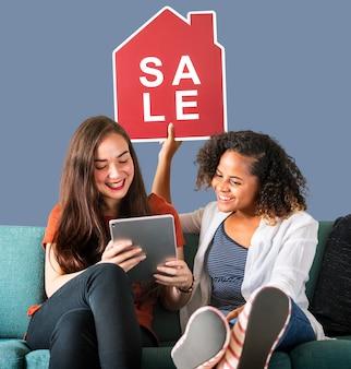 Vrouwen die een pictogram van de huisverkoop houden en een tablet gebruiken