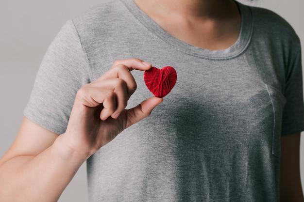 Vrouwen die een rood hart vasthouden en tonen. internationale of nationale cardiologiedag.