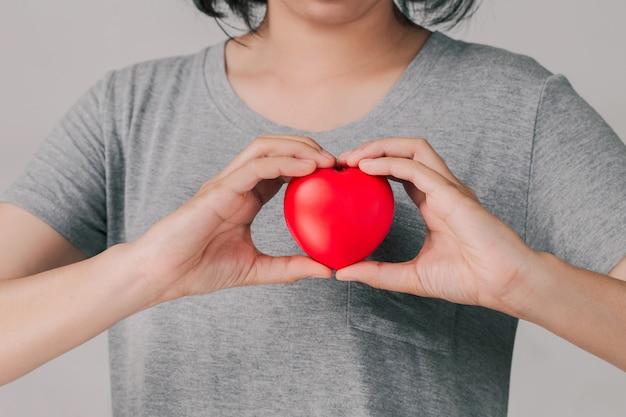 Vrouwen die een rood hart vasthouden en tonen.
