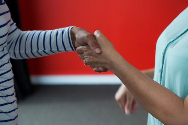 Vrouwen die elkaar de hand schudden in het kantoor