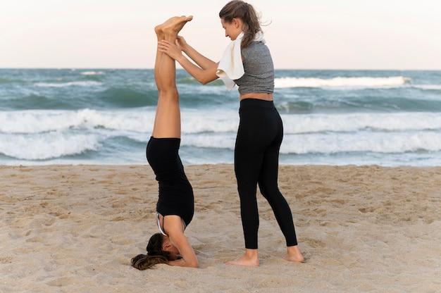 Vrouwen die elkaar helpen met hoofdhouding op het strand