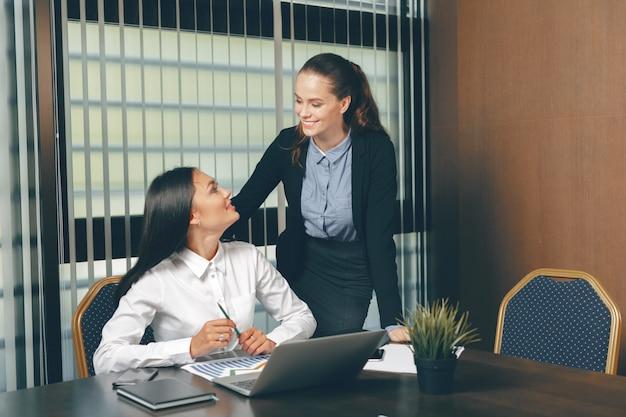 Vrouwen die financiële documenten in laptop lijst bekijken