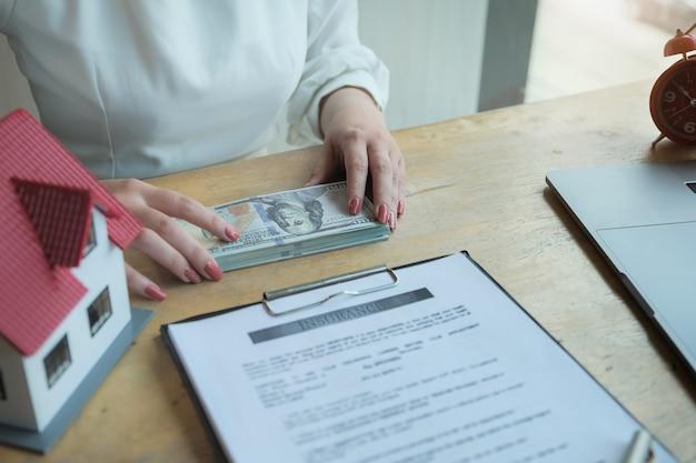 Vrouwen die geld tellen om een opstalverzekering voor een verzekeringsmaatschappij te betalen. contract en overeenkomst over verzekeringsconcepten.