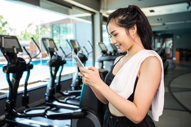 Vrouwen die gelukkig het spelen van de telefoon in de gymnastiek bevinden.
