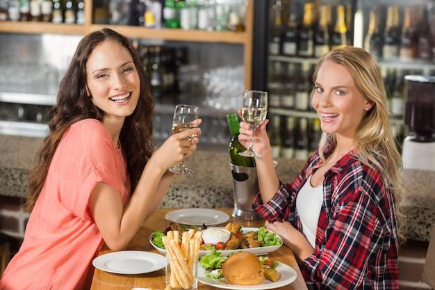 Vrouwen die glazen witte wijn houden