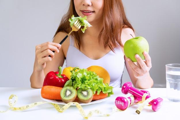Vrouwen die groente eten terwijl het houden van groene appel met fruit, groenten, water, domoor en meetlint op witte lijst. selectie van gezonde voeding. schoon eten en bewegen concept.