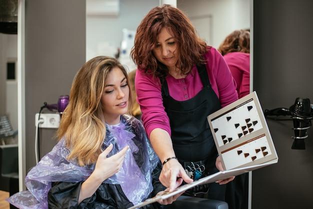 Vrouwen die haarkleur in kleurstofcatalogus kiezen