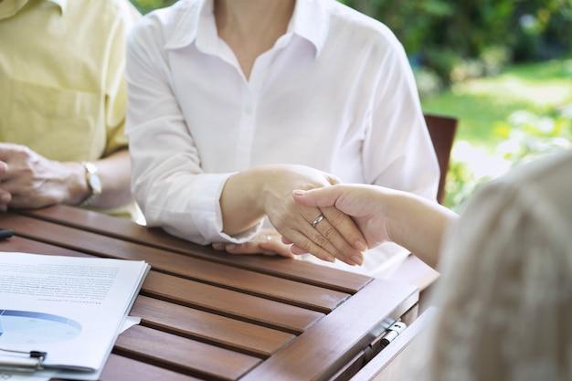 Vrouwen die handen schudden vertegenwoordigen verkoop, aziatische paarvergadering overleg met verzekeringsagent huidige analysegegevens de grafieken en grafieken, individuele aangifte inkomstenbelasting, financieel bedrijfsrapport.